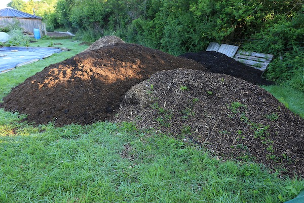 Heaps of woodchip, cow manure still hot and green waste compost